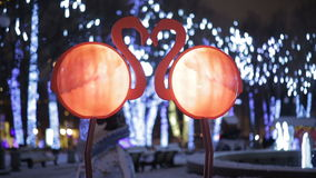 Two pink flamingos decoration on a celebration street. New Year and Christmas street decoration background stock video