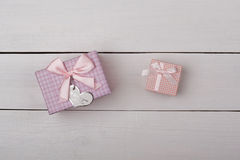 Two pink gifts with bows on white wooden table. Stock Images