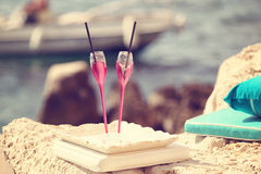 Two pink glasses on bech. Capture of Two pink glasses on bech Royalty Free Stock Photo