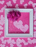 Two pink harts that say you and me are in the frame with flowers. And sparkles Stock Image
