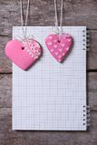 Two pink heart cookies and a note on a wooden board Royalty Free Stock Photos