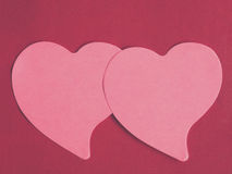 Two pink heart-shaped notepad on red leather background Stock Images