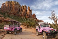 Two Pink Jeep Terrain Vehicles Sedona Arizona Slickrock Trail. Two Pink Jeep Off Road Terrain Vehicles with Tourists touring Broken Arrow Slick Rock near Sedona royalty free stock image