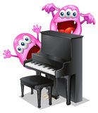 Two pink monsters at the back of the piano Stock Image