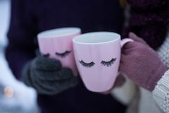 Two pink mugs with eyelashes in the hands of people stock photo