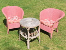 Two Pink Outdoor Chairs and Table sitting on the grass. Two pink outdoor chairs and brown table sitting outside on the grass Royalty Free Stock Photos