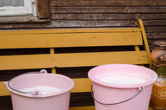Two pink pail full fresh cow milk on wooden bench Royalty Free Stock Images