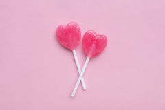 Two Pink Valentine`s day heart shape lollipop candy on empty pastel pink paper background. Love Concept. top view. Minimalism colorful hipster style royalty free stock image