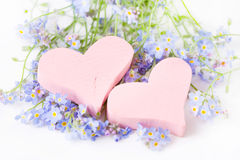 Two pink wooden hearts among wildflowers for greeting card. Royalty Free Stock Photo