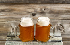 Two pints of fresh cold beer on top of wooden crate with rustic Royalty Free Stock Photography