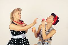 Two pinup girl friends playing with soap bubbles on white background.  stock photo