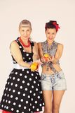 Two pinup girlfriends are holding oranges in their hands, offering them. Two pinup girlfriends are holding oranges in their hands, offering it stock photography