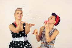 Two pinup girlfriends playing with soap bubbles.  stock images