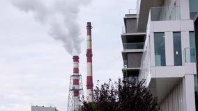 Two pipes of the heating station release white steam among modern city buildings at sunny day. Ecology concept stock video