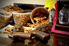 Guns in Home Environment. Two pistols laying on a kitchen counter by a coffee pot in a home environment. Empty brass casings in the background. Shallow depth of stock images
