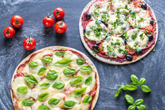 Two pizzas with ingredients on the wooden background Royalty Free Stock Images