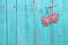 Two plaid country hearts hanging on antique teal blue wood door. Two red checkered hearts hanging from rope on vintage green wooden fence Stock Photo