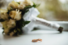 Two plain golden wedding rings. Two golden wedding rings with a bouquet on background Stock Photos