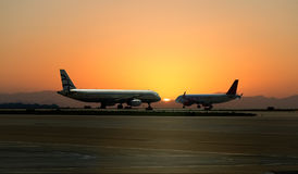 Two planes on the background of sunset at the airport in Attica Greece, April 2015 Stock Photos