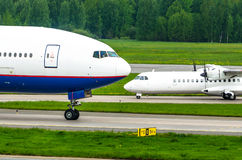 Two planes are big and small. Noses of aircraft at the airport Royalty Free Stock Photos
