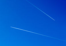 Two Planes in Blue Sky. Aeroplanes flying through clear blue sky with vapour trails Stock Photo