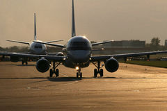 Two planes on runway. In airport. Photo is taken with interesting light Royalty Free Stock Images
