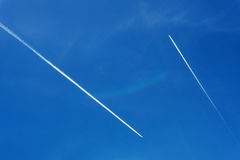 Two planes in the sky. Two planes crossing in a blue sky with white smoke trail Royalty Free Stock Images
