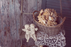 Two plaster angels in the arms sitting on a bench on a vintage b. Ackground of old wooden planks Royalty Free Stock Photo
