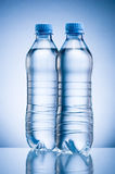 Two plastic bottle of drinking water  on blue background Stock Images
