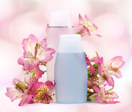 Two plastic bottles  and pink flowers Royalty Free Stock Images