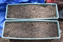 Two Plastic, Dirt Filled Planter Boxes. Two dirt filled, plastic planter boxes. Ready for planting stock photo