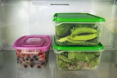 Two plastic food containers with green vegetable and one with berries on a shelf of a fridge. Stock Photo