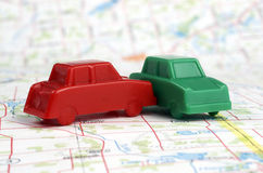 Two Plastic Game Token Sized Cars Colliding on a Map Stock Photos