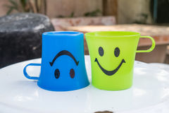 Two plastic glass with smile icon. On nature background royalty free stock photo