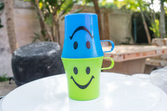 Two plastic glass with smile icon. On nature background royalty free stock image