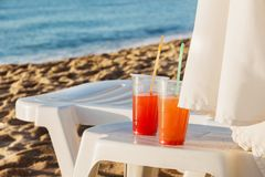 Two plastic glasses with bright drinks and cocktail tubes on a white table near the lounger stock photography