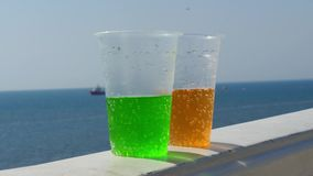 Two plastic glasses of lemonade against the background of the sea and the horizon. Sunny summer day. Cocktails of happiness, travel, relaxation on the beach stock footage