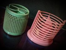 Two plastic pen stand. Different design and different color. stock image