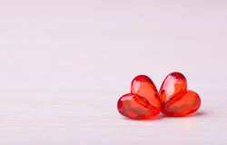 Two plastic red faceted hearts on light background Stock Image