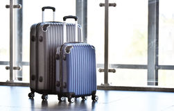 Two plastic travel suitcases in the airport hall Stock Photos