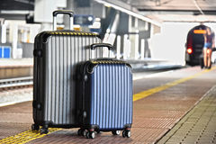 Two plastic travel suitcases on the railroad platform Royalty Free Stock Photo