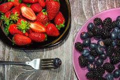 Two plates with berries. Heap of berries on two plates with a fork stock photos