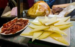 Two plates of cheese and jamon. Two plates of delicious slices of cheese and jamon ready to be served as tapas with some spanish wine royalty free stock images