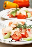 Two plates of colorful shrimp salad. Colorful shrimp salad with tomatoes, cucumber and some dill for garnish with bell peppers in the background Royalty Free Stock Images