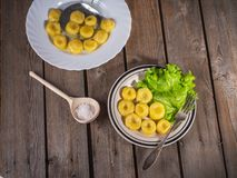 Two plates of cooked potato gnocchi with fresh leaf lettuce leaves, a fork on a plate. Near wooden spoon with coarse white salt stock photo