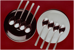Two plates and eight spoons Stock Images