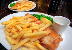 Two plates with fish and chips. Two plates with fish, chips, peas and sauce on a table Stock Photography