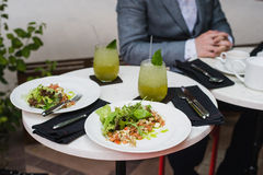 Two plates of fresh salad with arugula, mozzarella, vegetables, tomatoes, chicken served with mint lemonade in a small stock photo