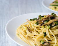 Two plates of pasta with mushrooms and green onions on a white plate. On a wooden table Stock Photo