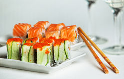 Two plates of salmon and cucumber sushi rolls Royalty Free Stock Images